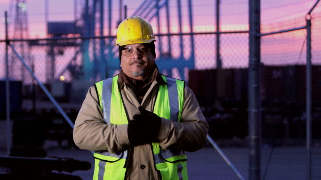 mature hispanic man working at shipping port, serious - health and safety stock videos & royalty-free footage