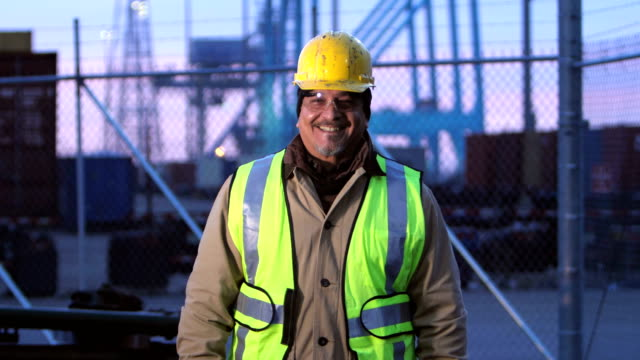 Mature Hispanic man working at shipping port, smiles
