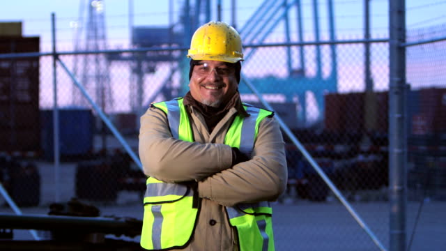 Mature Hispanic man working at shipping port, smiling