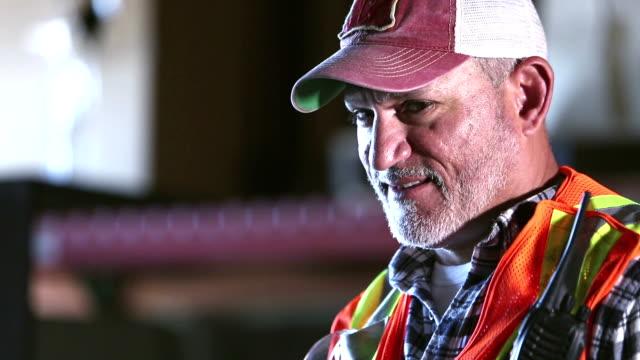 mature hispanic man working in warehouse - trucker cap stock videos & royalty-free footage