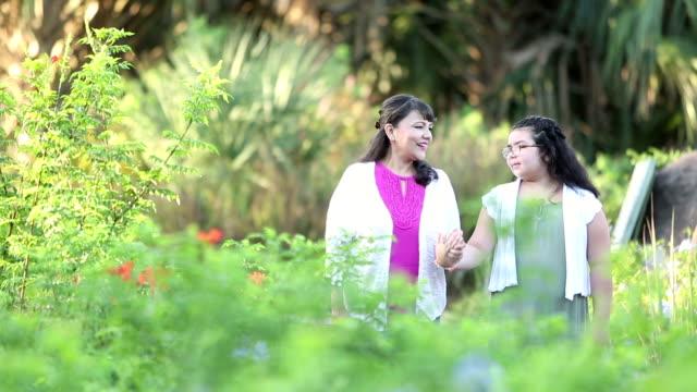 mature hispanic woman, granddaughter, walking in park - granddaughter stock videos & royalty-free footage