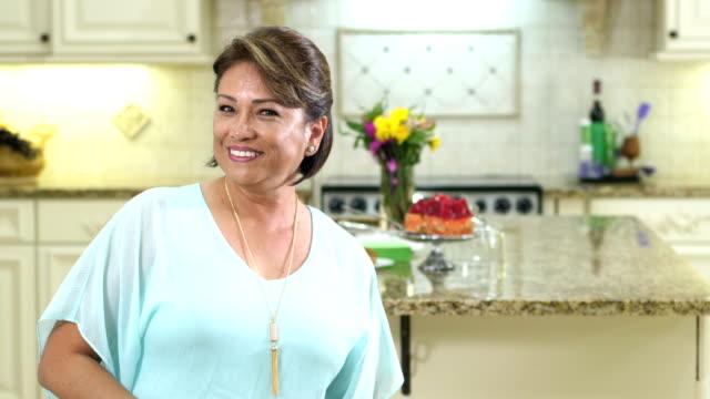 mature hispanic woman in kitchen smiling at camera - granite stock videos & royalty-free footage