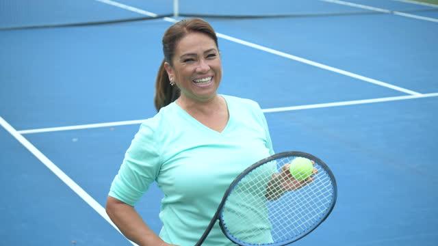 mature hispanic woman on tennis court - tennis racket stock videos & royalty-free footage