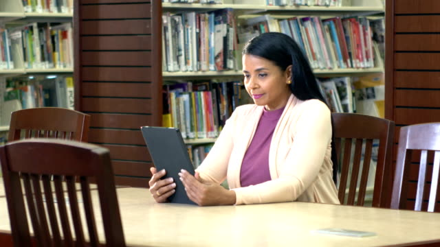 mature hispanic woman reading e-reader in library - e book stock videos & royalty-free footage