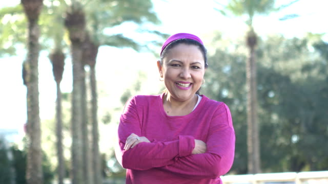 mature hispanic woman wearing pink sweatshirt - hand on hip stock videos & royalty-free footage