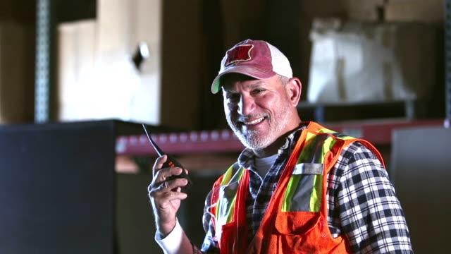 mature hispanic worker talking on walkie-talkie - trucker cap stock videos & royalty-free footage