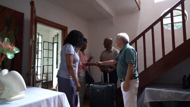 vídeos y material grabado en eventos de stock de maduro anfitrión bienvenido invitado familia africana en casa alquiler y alojamiento - alojamiento y desayuno