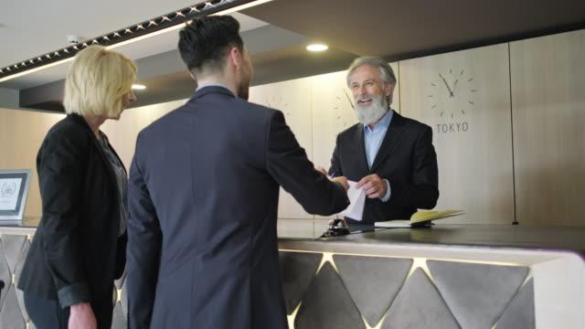 reife hotel rezeption ist shaking hände mit männlichen gast - gast stock-videos und b-roll-filmmaterial