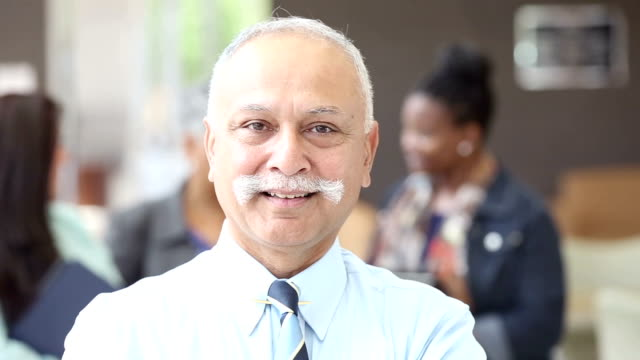 Mature Indian businessman walking into focus, in front of team