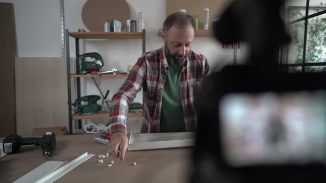 vídeos de stock e filmes b-roll de mature influencer vlogging about diy project from home - one mature man only