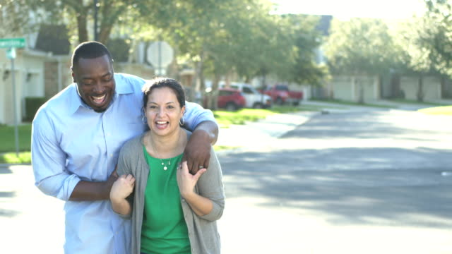 Mature interracial couple on residential street laughing