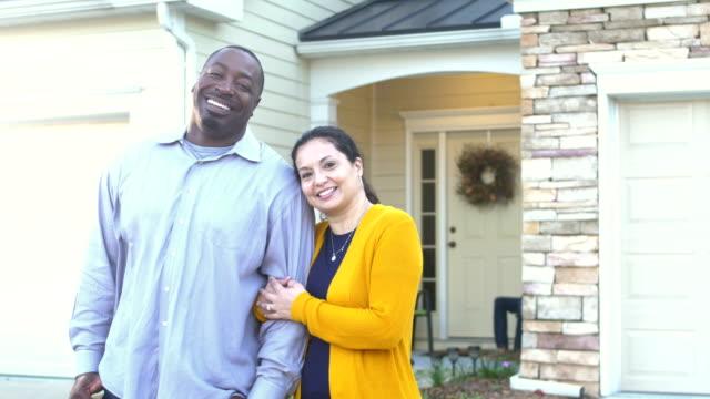 vídeos de stock e filmes b-roll de mature interracial couple, proud homeowners - em frente de