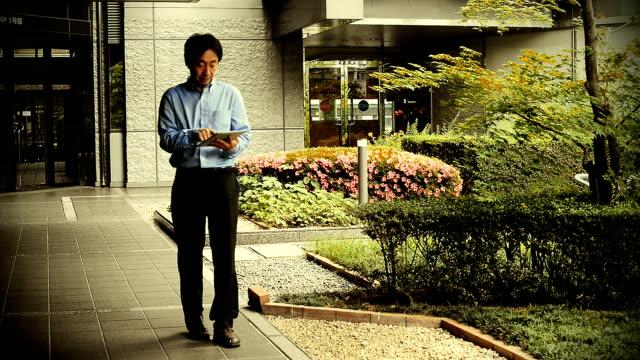 Mature Japanese businessman using digital tablet in modern office building