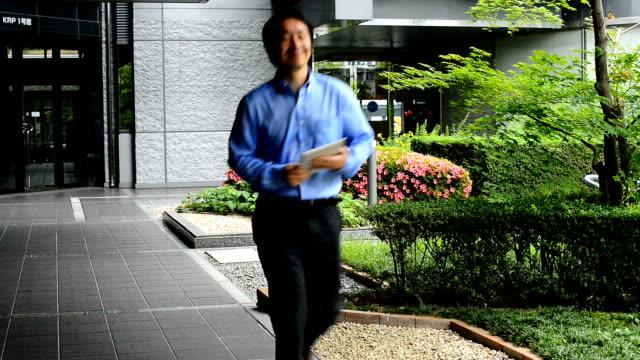 日本をマチュア実業家デジタルタブレットでモダンなオフィスビル - 中年の男性一人点の映像素材/bロール