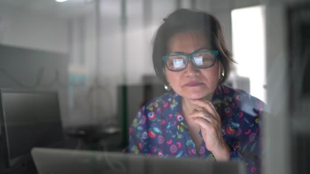 reife japanische mitarbeiter arbeiten auf laptop in der industrie - business finance and industry stock-videos und b-roll-filmmaterial