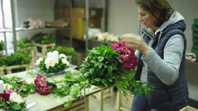 Mature lady florist working in flower workshop