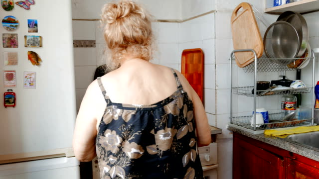 Mature lady preparing food in the kitchen