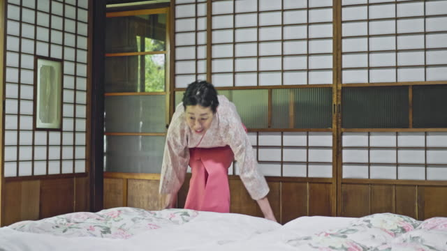Mature landlady laying futon in hotel room