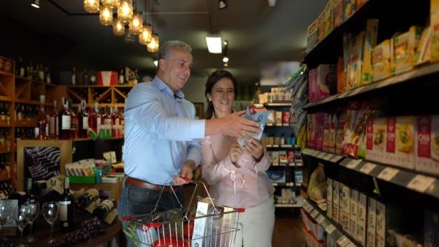vídeos de stock, filmes e b-roll de casal maturo latino-americanos, apreciando fazendo compras juntos enquanto homem carrega a cesta com produtos - gourmet