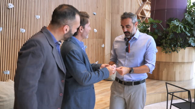 mature latin business people meet each other, handshake and exchange business cards - three people stock videos & royalty-free footage