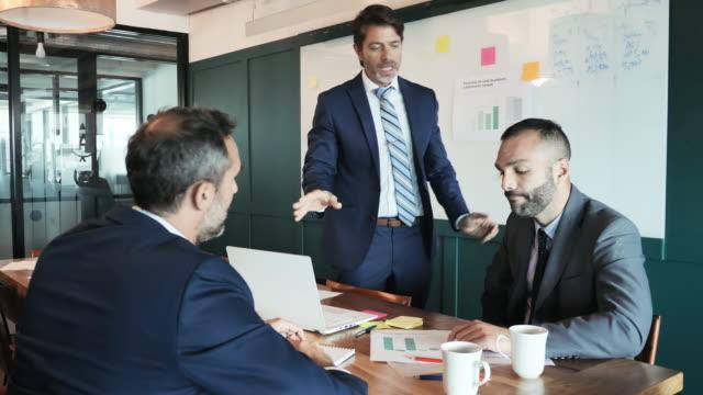 vídeos de stock, filmes e b-roll de empresário latino maduro explica nova estratégia de negócios - três pessoas