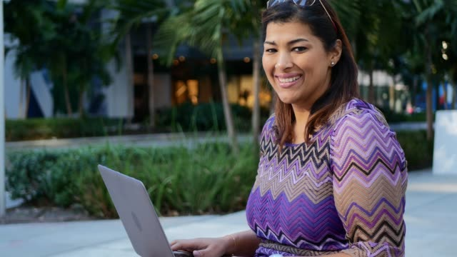 Mature Latina businesswoman in the financial district in USA, using laptop during the break