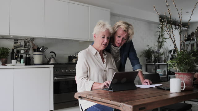 Mature lesbian couple looking at digital tablet together at home