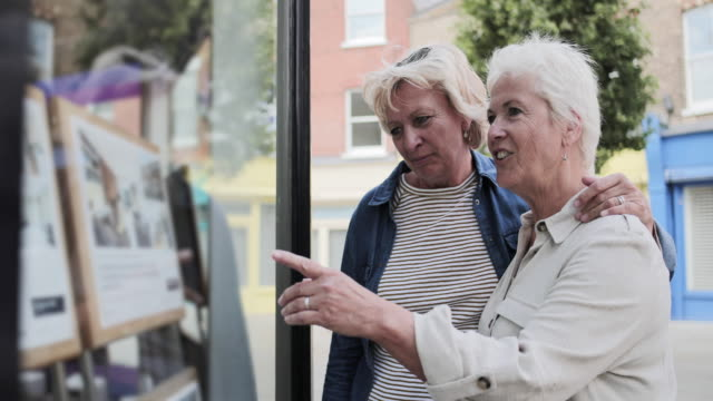 mature lesbian couple looking at real estate agency window - estate agent stock videos & royalty-free footage