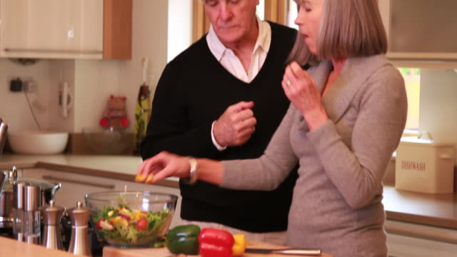 Mature male and female cooking together in kitchen