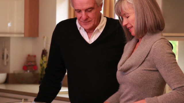 mature male and female cooking together in kitchen - open house stock videos & royalty-free footage