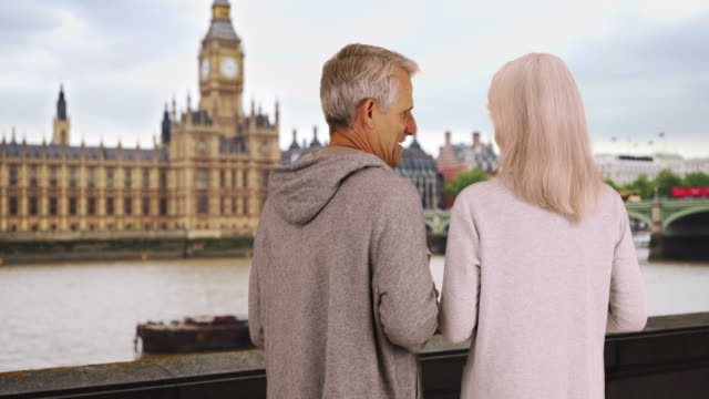 mature male and female drinking coffee and chatting by the river thames - coffee drink stock videos & royalty-free footage