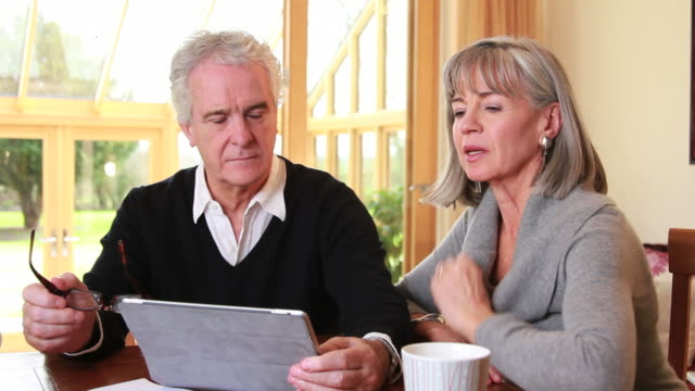 mature male and female looking at computer tablet - mature couple stock videos & royalty-free footage