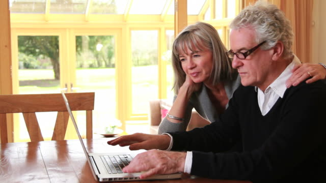 femmina e maschio maturo guardando portatile - coppia di età matura video stock e b–roll