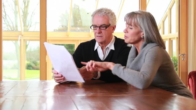stockvideo's en b-roll-footage met mature male and female looking at paperwork - pensioen thema
