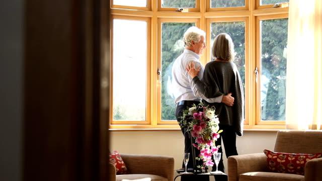 Ältere Männliche und weibliche Blick aus dem Fenster