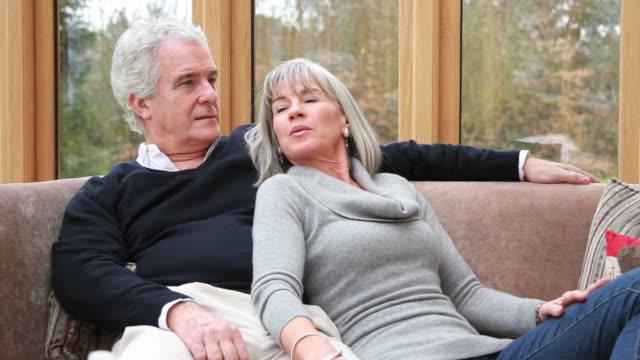 maschio e femmina maturo parlando sul divano - coppia di età matura video stock e b–roll