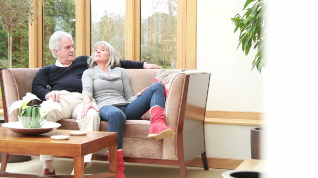 Mature male and female talking on sofa