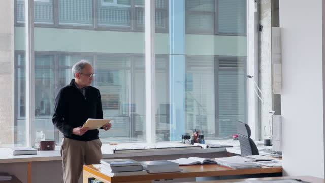ms mature male architect standing at desk in office holding folder/seattle, washington, usa - representing stock videos & royalty-free footage