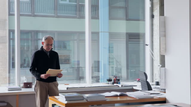 MS Mature male architect standing at desk in office holding folder/Seattle, Washington, USA