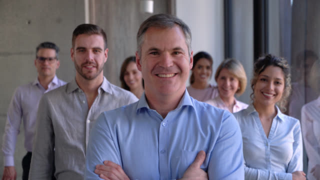 mature male business leader standing in front smiling at camera with arms crossed and his team standing at background - arms crossed stock videos & royalty-free footage