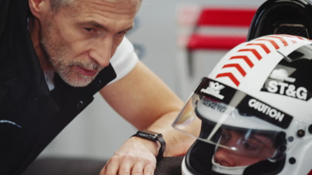mature male coach talking to racer at pit stop - crash helmet stock videos and b-roll footage