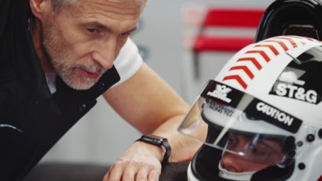 mature male coach talking to racer at pit stop - casco da motociclista video stock e b–roll
