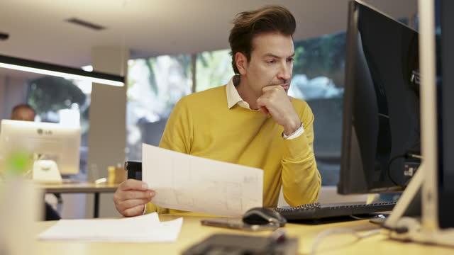 Designer masculino maduro trabalhando com planos na frente do monitor de computador