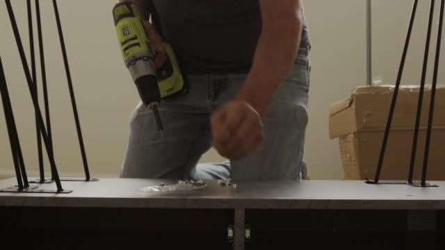 vídeos de stock e filmes b-roll de mature male diy furniture assembly with battery powered power tool drill 4k video series - secretária mobília