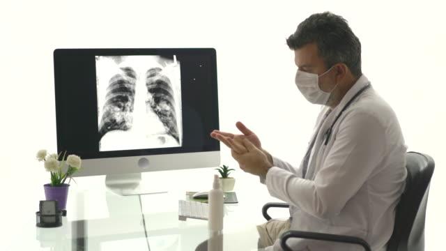 vidéos et rushes de médecin mâle mûr désinfectant sa main et vérifiant le film de radiographie de coffre à l'hôpital. - poumon humain