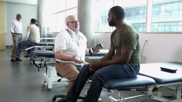 mature male doctor talks with military soldier about his health - clinica medica video stock e b–roll