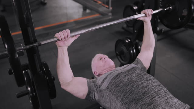 Mature male doing bench press at the gym