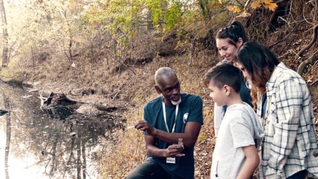 vídeos y material grabado en eventos de stock de el ambientalista macho maduro prueba la calidad del agua en el estanque - conservacionista
