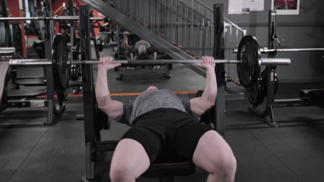 vídeos y material grabado en eventos de stock de mature male finishing using bench press at the gym - press de banca