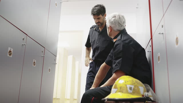 mature male firefighter talking with teammate in locker room - emotional support stock videos & royalty-free footage